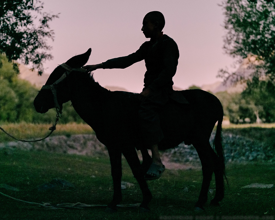 Kid on his donkey. The traditional life of the Wakhi people, in the Wakhan corridor, amongst the Pamir mountains.