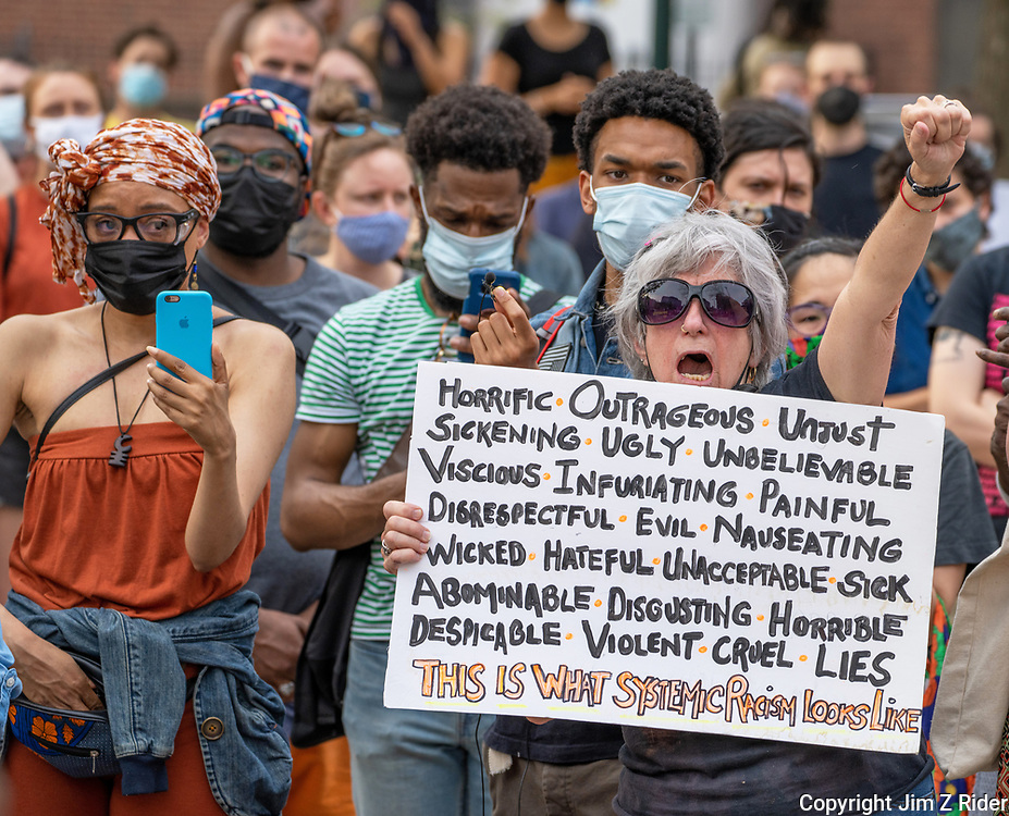 A protester spells out her message on a sign during a MOVE protest on the Penn campus.