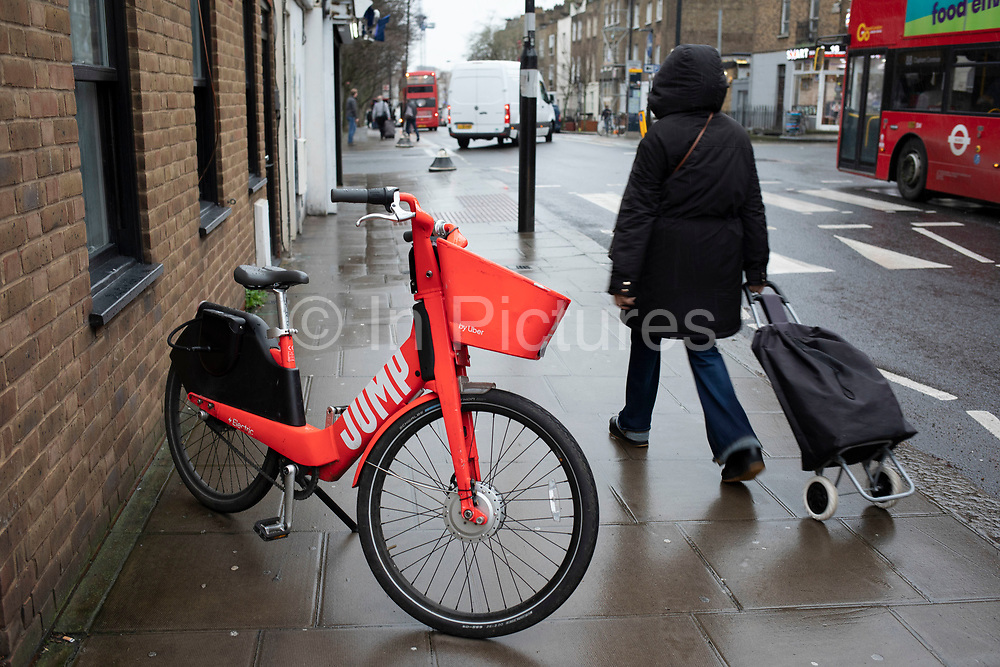 Jump dockless bike sharing electric cycle blocking the pavement on 14th January 2020 in London, England, United Kingdom. Social Bicycles Inc. doing business as Jump, is a dockless scooter and electric bicycle sharing system operating in the United States, Germany, Portugal and the United Kingdom. The bikes are a bright red orange. They can be located using the Jump or Uber apps, and users are charged to their Uber account.