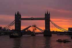 © Licensed to London News Pictures. 24/01/2014. London, UK. A pink and orange sky behind a raised Tower Bridge, just before sunrise this morning.  Unsettled weather and rain are forecast from today, following a period of unseasonably mild weather this January. Photo credit : Vickie Flores/LNP