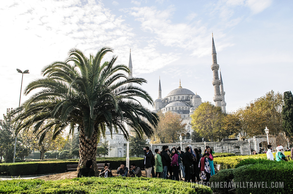 Tourists gather in under the sahde of a palm tree in Sultanahment Park with the Blue Mosque in the background. Sultan Ahmed Mosque (Turkish: Sultanahmet Camii) known popularly as the Blue Mosque is a Muslim (Sunni) Mosque in the center of Istanbul's old town district of Sultanahmet. It was commissioned by Sultan Ahmed I and completed in 1616,