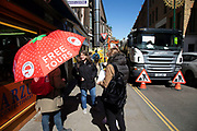 Free tours umbrella in the sunshine on Brick Lane in London, England, United Kingdom. However, the road is blocked due to construction and the tour takes a break.
