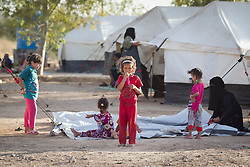 © Licensed to London News Pictures. 25/06/2014. Khanaqin, Iraq. A young Iraqi refugee plays with a balloon at a refugee camp on the outskirts of Bahari Taza village in Iraq. Located on the outskirts of Khanaqin, a town just 20 minutes from the front-line of the battle with ISIS insurgents, the Bahari Taza refugee camp, and its satellite camps, now house around 600 families from southern Iraq. Built by the local village leader to meet the influx of refugees from nearby Jalawla and Saidia, where intense fighting is still taking place. Turkman, Arab and Kurd, both Sunni and Shia, all live together in tents, barns and unfinished buildings waiting for the conflict to end. Photo credit: Matt Cetti-Roberts/LNP