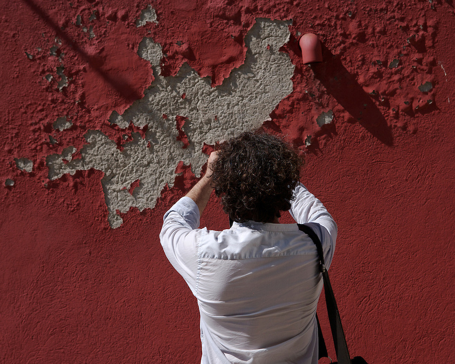 A tourist taking picture of flaking paint seen from behind