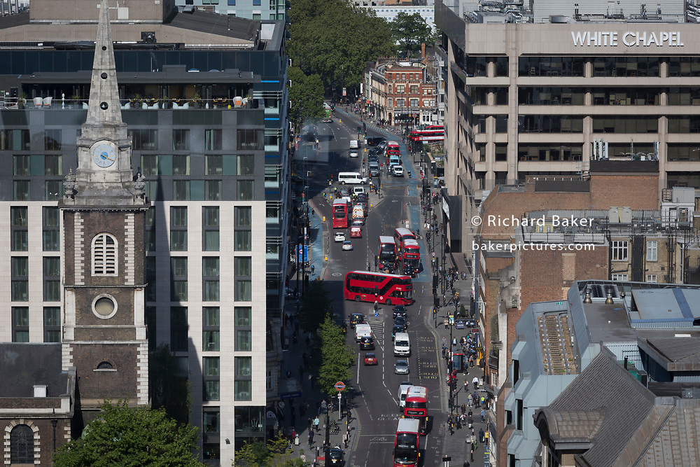 An aerial view eastwards to the church of St. Botolph's Aldgate and the A11 Whitechapel Road in the East End, from Aldgate and the City of London, the capital's ancient financial district, on 13th May, in London, England.