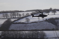 ***CAPTION CORRECTION***© Licensed to London News Pictures. 14/01/2015. Wheddon Cross, Somerset, UK. An Apache military helicopter  performing low-level manoeuvres near Wheddon Cross near Exmoor National Park in Somerset this morning, 14th January 2015. Snow has fallen overnight across many parts of England, causing travel disruption in some areas.  Photo credit : Rob Arnold/LNP