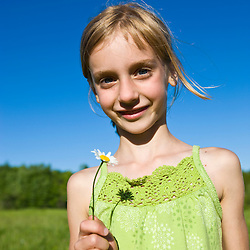 A young girl with a daisy in a field in Sabins Pasutre in Montpelier, Vermont.