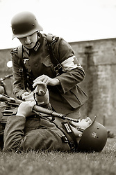 Greman Heer medic treats simulated casualty during battle reenactment Nww2A Fort Paull<br /> <br />  Copyright Paul David Drabble<br /> 5th & 6th May 2019<br />  www.pauldaviddrabble.co.uk
