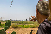 urban development is creeping up and consuming arable land. The farmer points to the new city being built near his fields. Photographed in Haniel [a moshav in central Israel. Located in the Sharon plain near Netanya and Kfar Yona], Israel