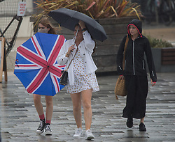 © Licensed to London News Pictures.  05/08/2021. Bournemouth, UK. Holiday makers walk along the sea front on a rainy day in Bournemouth, Dorset. Photo credit: Marcin Nowak/LNP