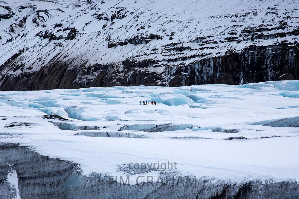Group of tourists walking on adventure trek on Svinafellsjokull glacier an outlet glacier of Vatnajokull, South Iceland