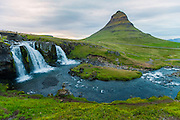 Kirkufellfoss - waterfall flows around the loan  pyramidal mountain Kirkufell on the Snaefellesness Pennisula of Iceland