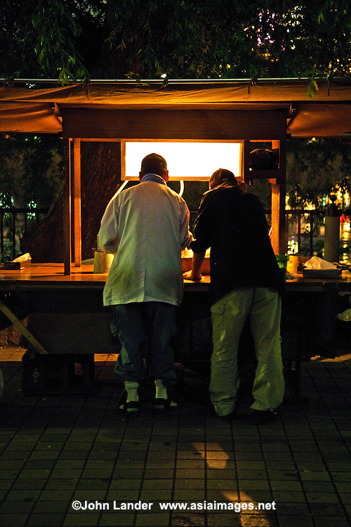 """A yatai is a small, mobile food stall typically selling ramen or oden. The name literally means """"shop stand."""" The stall is set up in the early evening on sidewalks and removed late at night or in the early morning hours. Beer, sake and shochu are usually available. A salaryman might relax with colleagues over dinner and drinks at a yatai on his way home from work. Fukuoka is well known in Japan for keeping the yatai tradition alive."""