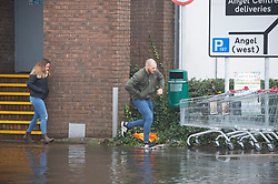 ©Licensed to London News Pictures 22/12/2019. <br /> Tonbridge ,UK. Man jumping flood water, Angel car park.  Mountain bikers enjoying the water. Heavy rain over night has caused more Christmas flooding in Kent.  Christmas shoppers in Tonbridge, Kent are facing severe disruption in the town centre with two car parks, roads and pathways all flooded and out of action as the River Medway bursts its banks. Photo credit: Grant Falvey/LNP