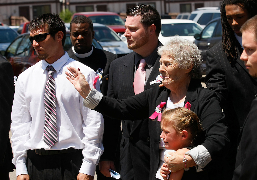 Marlene Knobbe grandmother of Micayla Medek killed in the July 20, 2012 movie theater shooting waves as Medek's casket is loaded into a hearse after her funeral in Aurora July 26, 2012.  At left is Medek cousin James Vigil, 2nd left is her brother Shane and Rachel Vigil, second cousin in lower right. REUTERS/Rick Wilking (UNITED STATES)