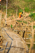 11 MARCH 2013 - LUANG PRABANG, LAOS:  A Buddhist novice walks up a hill after crossing the bamboo foot bridge over the Nam Khan River in Luang Prabang. The bridge is a seasonal bridge. It's built when the river level recedes in the dry season and washes away every year when the river rises. It connects Luang Prabang to several small villages north of the city.   PHOTO BY JACK KURTZ