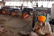 A men relaxes sipping a chai, the indian masala tea. In the background three huge brick ovens incessantly cook thousands litres of spicy sauces.