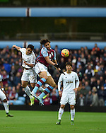 Jefferson Montero of Swansea city (20) jumps for a header with Rudy Gestede of Aston Villa. Barclays Premier league match, Aston Villa v Swansea city at Villa Park in Birmingham, the Midlands on Saturday 24th October 2015.<br /> pic by  Andrew Orchard, Andrew Orchard sports photography.