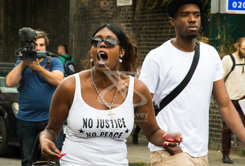 Tottenham, London, August 4th 2015. Family, friends and supporters of alleged gangster Mark Duggan, who was shot and killed by police on 4th August 2011 in Tottenham, commemorate his death which led to widespread uprisings and riots, by marching from Broadwater Farm estate to Tottenham police station. His family is demanding a public inquiry into the role of Operation Trident, set up to fight gun and knife crime amongst the black community, whose officers they accuse of putting guns out on the streets of London. PICTURED: A woman hurls abuse at police officers brought in to control the traffic.  // Contact: paul@pauldaveycreative.co.uk Mobile 07966 016 296