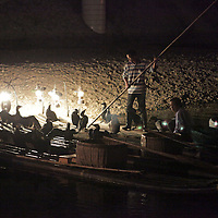 Asia, China, Guilin. Rafts and cormorants lined up for fishing by lantern.