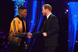 Prince Harry, right, greets Donel Mangena on stage at the Royal Albert Hall in London for a star-studded concert to celebrate the Queen's 92nd birthday.