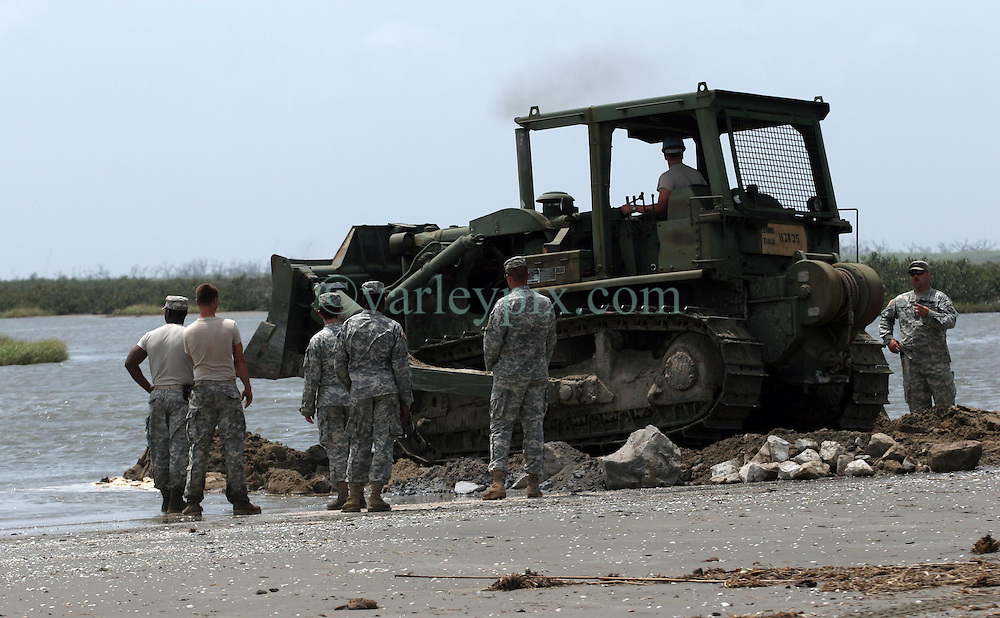 13 May 2010. Elmer Island, Lafourche Parish, Louisiana. <br /> Like King Canute before them, Louisiana National Guardsmen of the 922nd Horizontal Engineer Company, 769th Engineer Battalion fight a losing battle against mother nature as they battle against the strong currents to close the inland waterways from the ocean now depositing oil from the Deepwater Horizon catastrophe on the beaches. <br /> Photo credit; Charlie Varley/varleypix.com