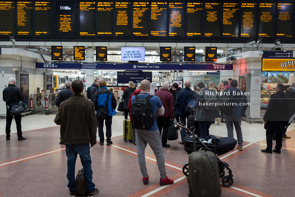 Rail passengers look up the information times of departures at Victoria station, on 8th November 2019, in London, England.