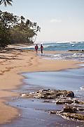 A couple walk down Steps beach in Rincon Puerto Rico