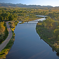 A bridge and dirt road cross a narrow section of the Jefferson River as it flows between pastures and cottonwood groves.  Just downstream at Three Forks, Montana, it joins the Madison and Gallatin Rivers to become the Missouri.