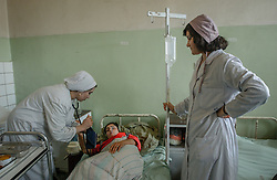 Doctors and nurses attend patients at the Rabia Balkhi hospital in Kabul, Afghanistan August 4, 2002. There is a severe shortage of female doctors in Afghanistan making it difficult for women and children to get adequate health care. Infant mortality in Afghanistan in 2000 was 165 per 1,000. live births - one of the highest figures in the world, according to the United Nations International Children's Fund (UNICEF). More than one if four children die before age 5. The U.S. infant mortality rate is 7 per 1,000. Half Afghanistan's children suffer from malnutrition. (Photo  by Ami Vitale)