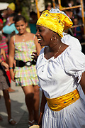 Cuban woman of African descent dancing, smiling as part of a performance. Performance in Havana old town, local dance and theatre group enacting the slave trade, colonial rule and how African religion and beliefs continuing, becoming what is now Santeria.