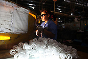 Workers make fluorescent light bulbs on an assembly line at a Technical Consumer Products, Inc (TCP) factory in Zhengjiang, China, on 30 August, 2010. TCP is one of the major exporters of fluorescent bulbs to the United States, which has made the bulbs the standard light source in the country.