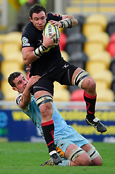 Dragons Number 8 (#8) Tom Brown is tackled by Northampton Flanker (#6) Calum Clark (capt) during the first half of the match - Photo mandatory by-line: Rogan Thomson/JMP - Tel: Mobile: 07966 386802 18/11/2012 - SPORT - RUGBY - Rodney Parade - Newport. Newport Gwent Dragons v Northampton Saints - LV= Cup Round 2