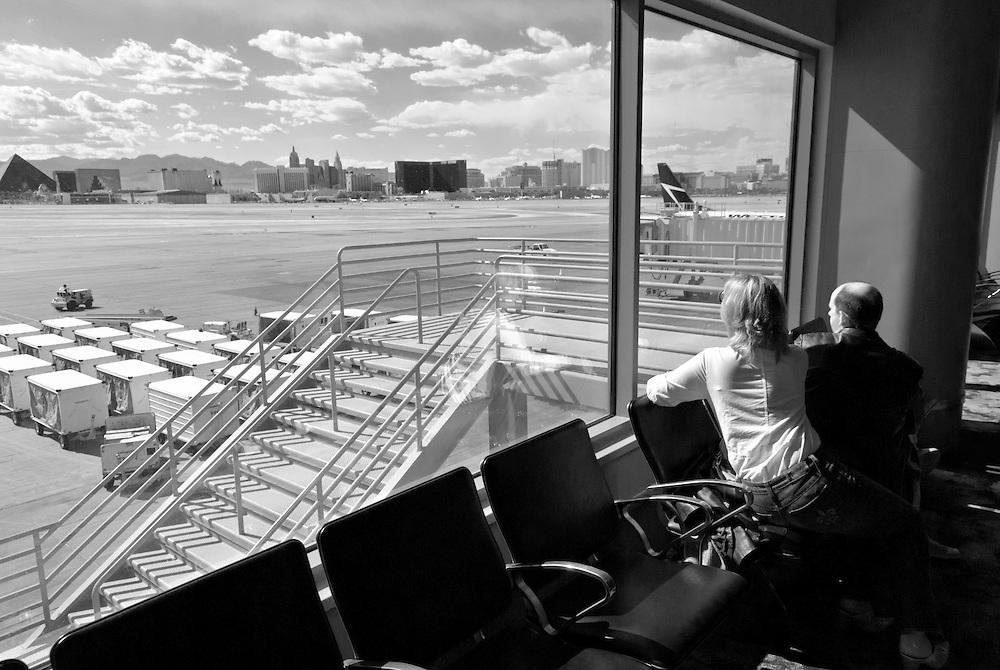 USA, Nevada, Las Vegas Flughafen, Ein Paar Blick durch die Glasscheiben der Abflughalle des Flughafens Las Vegas auf die Start- und Landebahn. Im Hintergrund die Skyline von Las Vegas. Am Horizont zeigt sich die Gebirgskette |Las Vegas Airport ,A couple views through the glass windows of the departure hall of Las Vegas Airport to the runway. In the background the skyline of Las Vegas and on the horizon the mountain range