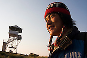 Trekking guide Bibek Gurung watches the sunrise at Poon Hill, a viewpoint along the Annapurna Sanctuary and Circuit Treks, Himalaya Mountains, Nepal. A viewing tower is visible in the background.