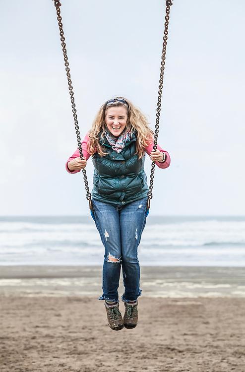 A middle aged woman swinging on a swing set on Seaside Beach, Oregon, USA.
