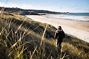 Woman enjoying a winter walk through the sand dunes at St Ouen's Bay, Jersey, towards Le Carriere beach and views out to Corbiere lighthouse.
