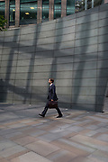 A man carries a briefcase in  modern architecture at Broadgate, on 10th May 2017, in the City of London, England.