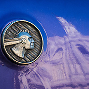 The capitol building in Havana reflected in the shiny paint of an old Pontiac, with the Pontiac indian logo.