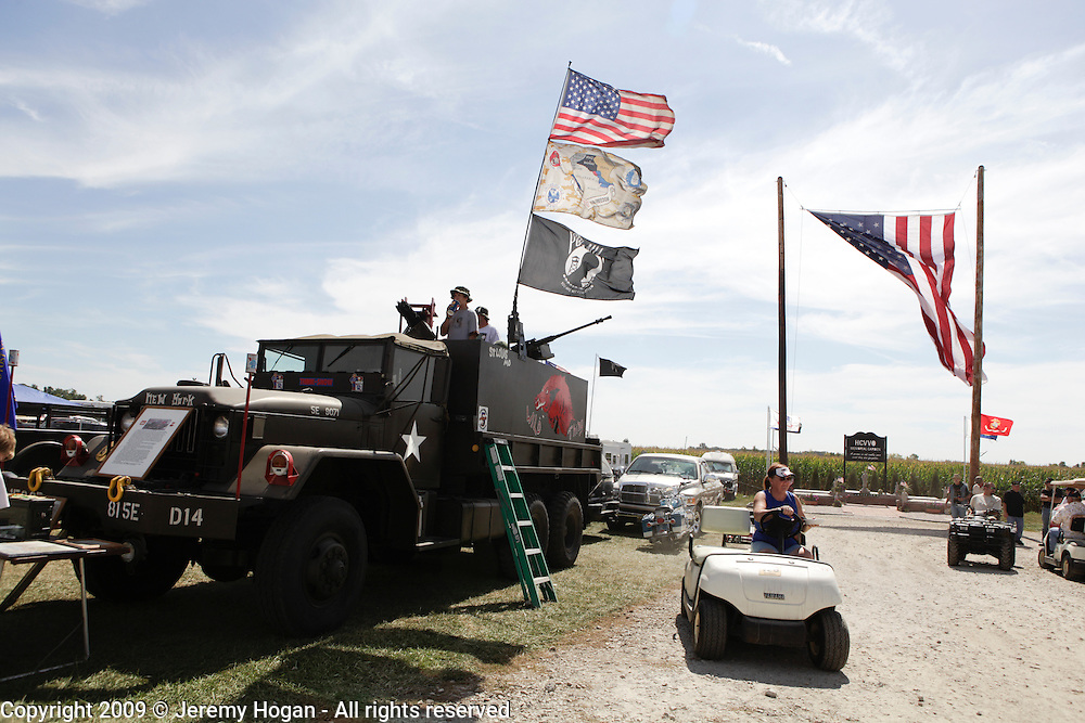 A gun truck left, and a large American flag are on display during the Vietnam Veterans gathering in Kokomo, Indiana for the 2009 reunion.