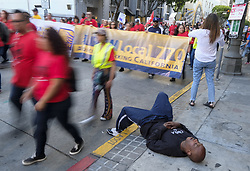 May 1, 2019 - Los Angeles, California, U.S - A man sleeps on the sidewalk, as thousands of workers rally on May Day in Los Angeles. (Credit Image: © Ringo Chiu/ZUMA Wire)