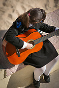 Young woman playing acoustic guitar on beach, Cadiz, Andalusia, Spain