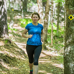 A woman trail running at the Shepards Farms Preserve in Norway, Maine.