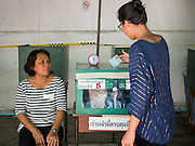 07 AUGUST 2016 - BANGKOK, THAILAND:  A woman drops her ballot into the ballot box at a polling place in a park in Bangkok. Thais voted Sunday in the referendum to approve a new charter (constitution) for Thailand. The new charter was written by a government appointed panel after the military coup that deposed the elected civilian government in May, 2014. The charter referendum is the first country wide election since the coup.      PHOTO BY JACK KURTZ