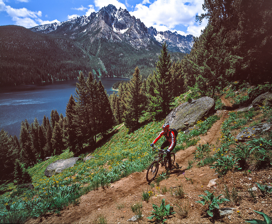 Mountain biker climbs the switch back trail up from Redfish Lake with the Grand Mogul looming in the background at 9733 in the Sawtooth Mountain of Central Idaho