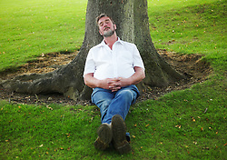 © Licensed to London News Pictures.14/07/15<br /> Harrogate, UK. <br /> <br /> A man sleeps in the shade against a tree on the opening day of the Great Yorkshire Show.  <br /> <br /> England's premier agricultural show opened it's gates today for the start of three days of showcasing the best in British farming and the countryside.<br /> <br /> The event, which attracts over 130,000 visitors each year displays the cream of the country's livestock and offers numerous displays and events giving the chance for visitors to see many different countryside activities.<br /> <br /> Photo credit : Ian Forsyth/LNP