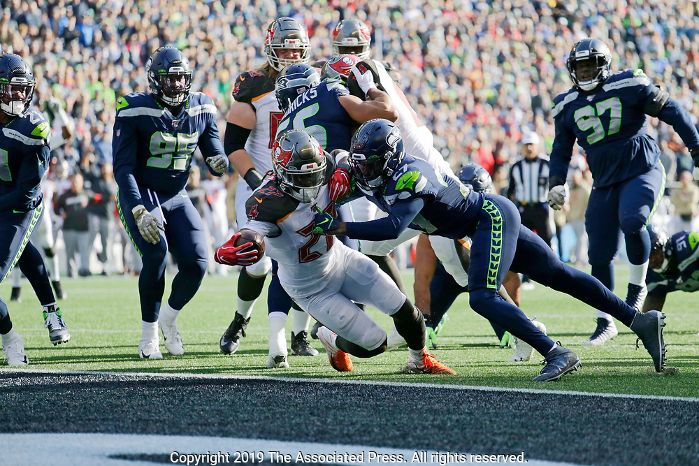 Tampa Bay Buccaneers running back Ronald Jones, lower-left, scores a touchdown ahead of Seattle Seahawks defensive back Marquise Blair, center-right,  during the first half of an NFL football game, Sunday, Nov. 3, 2019, in Seattle. (AP Photo/John Froschauer)