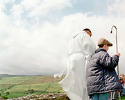 The vicar and a boy carrying a crook at the Lamb Service, Middlesmoor, Nidderdale, North Yorkshire, UK. Each year the villagers bring lambs to the church to celebrate the local farming community.
