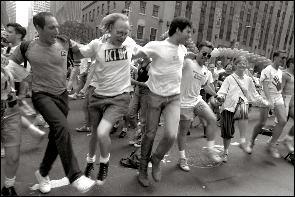 """G'dali Braverman, David Robinson, Mark Fisher, Natasha Gray and others of ACT UP NY, on June 24, 1989, the 20th anniversary of the Stonewall riots, participating in a renegade march up 6th avenue to Central Park. Themed, """"In The Tradition"""", this march followed the same route as the original march 20 years ago and was designed as a rebuke to the corporatization of the gay pride parade. Chanting """"2-4-6-8 How do you know the Rockettes are straight?!?"""" as they passed by Radio City Music Hall."""