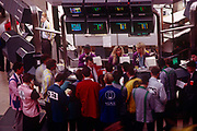 Active trading inside the London Stock Exchange in the City of London during the late-eighties. We see an aerial view of the 1980s-era options trading floor, looking  down from a high vantagepoint on to the traders as they go about their business. Three years after the so-called Big Bang in 1986 , this location at the old Stock Exchange Tower  became redundant with the advent of the Big Bang, which deregulated many of the Stock Exchange's activities as it enabled an increased use of computerised systems that allowed dealing rooms to take precedence over face to face trading. Thus, in 2004, the House moved to a brand new headquarters in Paternoster Square, close to St Paul's Cathedral.